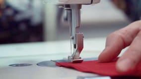 Detalle macro de trabajo de la máquina de coser la aguja mueve y cose la tela el corte del material en a almacen de metraje de vídeo