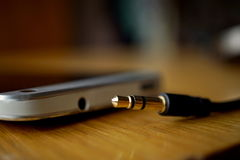 Detalle macro de un conector de auriculares del metal cerca el conector en el teléfono móvil, en la superficie de madera Imagenes de archivo