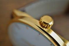 Detalle macro de un sistema mellado de oro de la corona en el reloj dorado como símbolo del reloj lujoso Fotografía de archivo libre de regalías