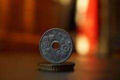 Detalle macro de un yen japonés de la moneda japonesa del metal en el top de la columna creado de monedas con un backgroun calien imagenes de archivo