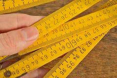 Detalle macro del metro de la cinta de metal amarillo con los números rojos y negros que miden longitud en centímetros Fotos de archivo libres de regalías