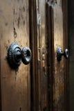 Detalle medieval medieval del tirador de puerta en puertas de madera antiguas con la pintura de la peladura Foto de archivo libre de regalías