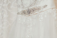 Detalle poner crema hermoso del vestido de boda con las flores Fotografía de archivo libre de regalías