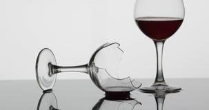 Detalle tirado de la copa de vino quebrada que est? poniendo en la superficie mojada almacen de metraje de vídeo