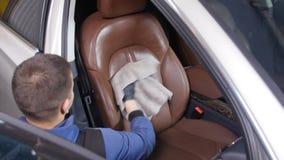 Detalle y limpieza de asientos delanteros interiores en los coches modernos de lujo Concepto del mantenimiento del coche almacen de metraje de vídeo