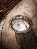 Detalle y primer de la vieja luz redonda del coche viejo cubierta con moho con la pintura agrietada Imagen de archivo libre de regalías