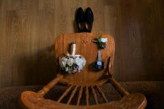 Detalles de la boda Accesorios del novio Zapatos, anillos, boutonniere y reloj en silla Fotos de archivo