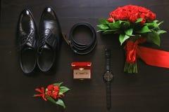 Detalles de la boda Accesorios del novio Zapatos, anillos, correa, boutonniere y reloj en la tabla Imagenes de archivo