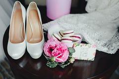 Detalles de la boda, decoración El ramo de rosas rosadas, los accesorios nupciales y los macarrones se colocan en una tabla de ma Imagen de archivo