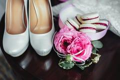 Detalles de la boda, decoración El ramo de rosas rosadas, los accesorios nupciales y los macarrones se colocan en una tabla de ma Foto de archivo libre de regalías