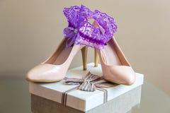 Detalles de la boda Liga púrpura en los deslizadores del ` s de la novia Rectángulo con un regalo Fotografía de archivo