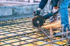 Detalles de la construcción con el trabajador que corta las barras de acero y el acero reforzado con la amoladora de ángulo Image imágenes de archivo libres de regalías