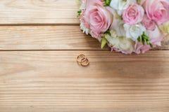 Detalles de la mañana del día de boda dos anillos de bodas del oro están en la tabla de madera marrón Imagen de archivo