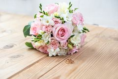 Detalles de la mañana del día de boda dos anillos de bodas del oro están en la tabla de madera marrón Imágenes de archivo libres de regalías