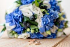 Detalles de la mañana del día de boda dos anillos de bodas del oro están en la tabla de madera marrón Fotografía de archivo libre de regalías