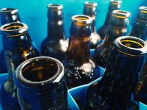 Detalles de las botellas de cristal en el plástico azul fotos de archivo