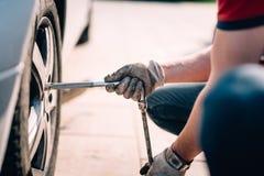 Detalles de los neumáticos cambiantes del mecánico, trabajando en taller y reparando en los automóviles fotografía de archivo