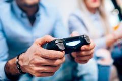 Detalles de manos usando regulador y jugar de la palanca de mando a juegos digitales del ordenador en la TV imagen de archivo libre de regalías