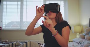 Detalles de un adolescente con el juego un juego virtual usando un VR en su sitio que pone en la cama y que pasa un rato divertid almacen de metraje de vídeo