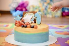 Detalles de una primera torta de cumpleaños del año en azul, para el muchacho imagen de archivo libre de regalías