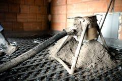 Detalles del mortero del cemento y de la bomba concreta durante construcciones interiores imagenes de archivo