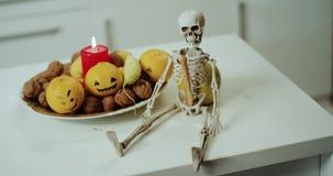 Detalles del primer de las decoraciones para Halloween, placa con las mini calabazas y velas, un esqueleto asustadizo almacen de metraje de vídeo