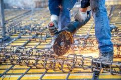 Detalles del sector de la construcción - el trabajador que cortaba las barras de acero usando el inglete de la amoladora de ángul Imagenes de archivo