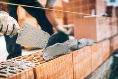Detalles del trabajador de construcción, engranaje protector y paleta con las paredes de ladrillo del edificio del mortero fotografía de archivo