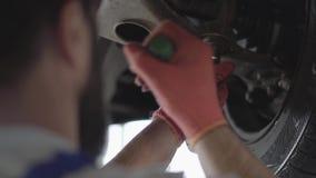 Detalles que atornillan barbudos del mecánico de coche del coche con el equipamiento especial en el automóvil levantado en el cie metrajes