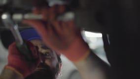 Detalles que atornillan profesionales del mecánico de coche del coche con la herramienta especial en el automóvil levantado en el almacen de metraje de vídeo