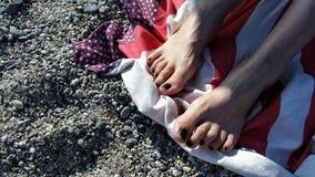 Detalles soleados de los pies de la muchacha en una toalla Fotos de archivo