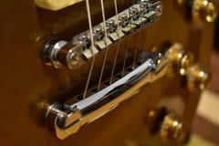 Detalles superiores de la guitarra del oro Secuencias, puente y primer de los botones foto de archivo
