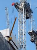 Detaol av en stor konstruktionskran som lyfter en stor metallstråle arkivbild
