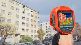 Detectando a perda de calor fora da construção foto de stock royalty free