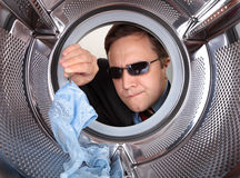 Detective. Searches through the dirty clothes in the washing machine Royalty Free Stock Photography