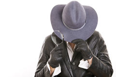 Detective. Woman dressed detective, covering her face with a hat, gloves and a magnifying glass. Isolated on a white background royalty free stock photos