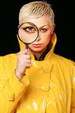 Detective. Girl in yellow mackintosh with magnifier Stock Photography