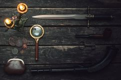 Detective agent table. Musket gun, magnifying glass, smoking pipe, wallet with coins, key, and burning candle on wooden table background royalty free stock photography