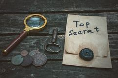 Detective agent table. Top secret documents file, key, magnifying glass and coins on the detective spy agent table background royalty free stock photography