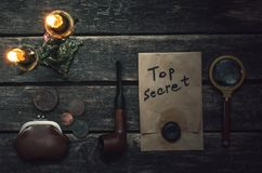 Detective agent table. Top secret documents file, key, magnifying glass, smoking pipe and wallet with coins on the detective spy agent table background royalty free stock photo