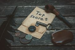 Detective agent table. Top secret documents file, key, smoking pipe, feather pen and wallet with coins on the detective spy agent table background stock images