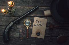 Detective agent table. Top secret documents file, magnifying glass, smoking pipe, bowler hat and wallet with coins on the detective spy agent stock photo