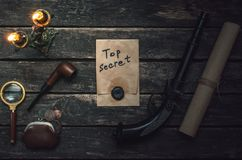 Detective agent table. Top secret documents file, magnifying glass, smoking pipe and wallet with coins on the detective spy agent royalty free stock photos