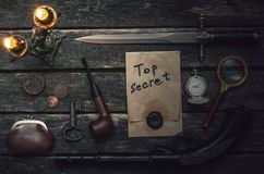 Detective agent table. Top secret documents file, musket gun, dagger, magnifying glass, smoking pipe, pocket watch and wallet with coins on the detective spy royalty free stock photos