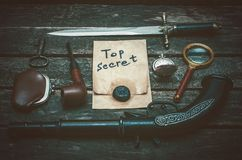 Detective agent table. Top secret documents file, musket gun, dagger, magnifying glass, smoking pipe, and wallet with coins on the detective spy agent stock photography