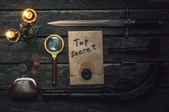 Detective agent table. Top secret documents file, musket gun, dagger, magnifying glass, smoking pipe, and wallet with coins on the detective spy agent stock images