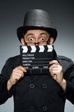 The detective in black coat with clapperboard Stock Photo