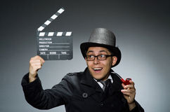 The detective in black coat with clapperboard Royalty Free Stock Photo