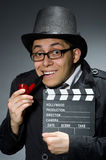 The detective in black coat with clapperboard Stock Image