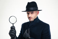 Detective in black coat, hat and gloves holding magnifying glass. Portrait of serious handsome detective in black coat, hat and gloves holding magnifying glass stock images